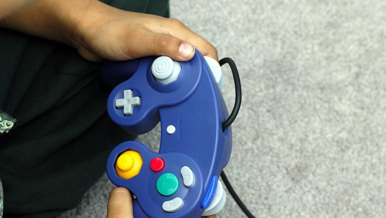 Un enfant joue à un jeu vidéo sur une console de jeu GameCube de Nintendo
