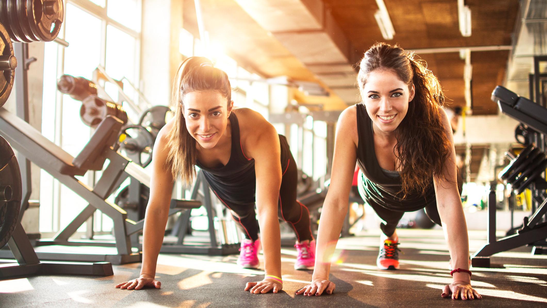 femmes-sourire-salle-de-sport-gainage-planche-fitness
